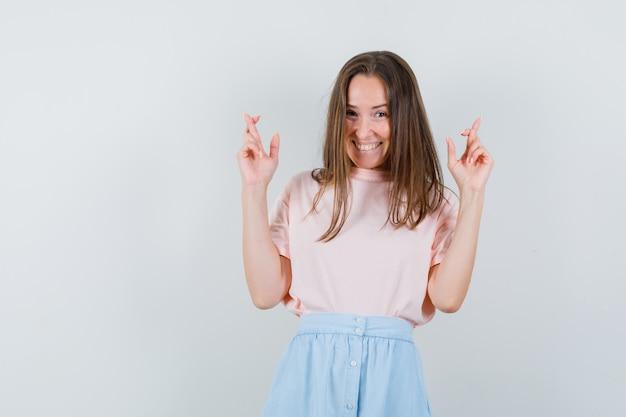 Jeune femme gardant les doigts croisés en t-shirt, jupe et à la chance, vue de face.