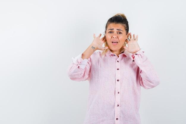 Jeune femme en gardant les doigts derrière les oreilles en chemise rose et à la confusion