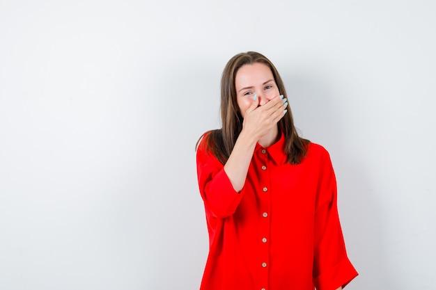 Jeune femme gardant la main sur la bouche en chemisier rouge et l'air joyeux, vue de face.