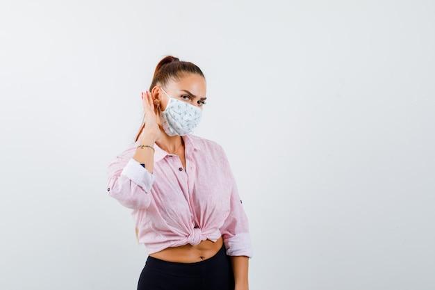 Jeune femme gardant la main derrière l'oreille en chemise, pantalon, masque et à la curieuse. vue de face.