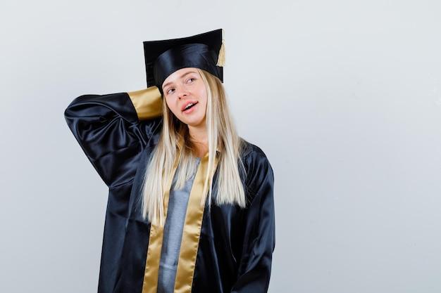 Jeune femme gardant la main derrière la tête en uniforme de diplômé et à la recherche de rêve.
