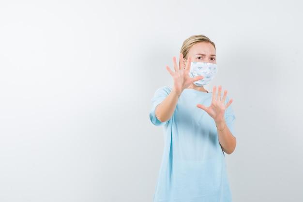 Jeune femme gardant la main pour se défendre en t-shirt, masque et semblant anxieuse