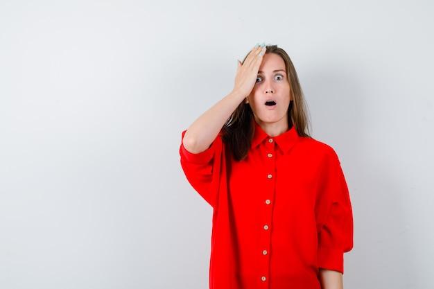 Jeune femme gardant la main sur la tête en chemisier rouge et l'air choqué. vue de face.