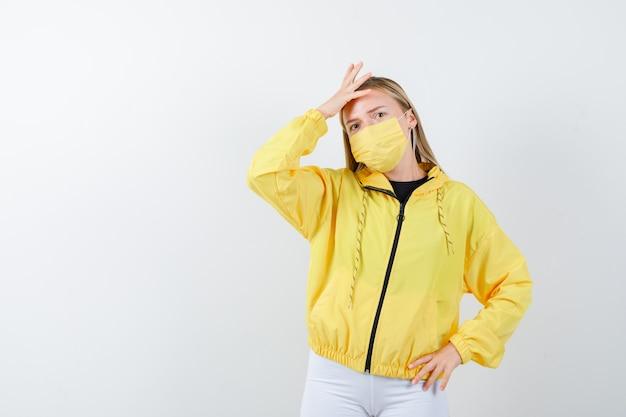 Jeune femme gardant la main sur la tête en veste, pantalon, masque et regardant pensif, vue de face.
