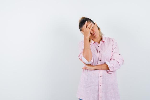 Jeune femme gardant la main sur le visage en chemise rose et à la colère