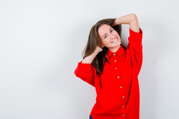 Jeune femme gardant les mains dans les cheveux en chemisier rouge et l'air heureux, vue de face.