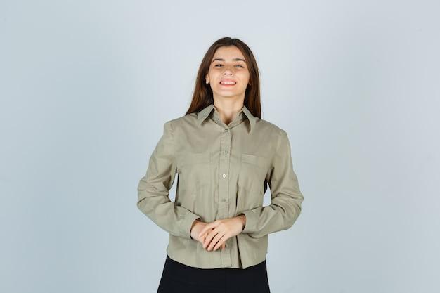 Jeune femme gardant les mains devant elle en chemise, jupe et à la joyeuse