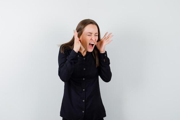 Jeune femme gardant les mains levées près du visage en criant