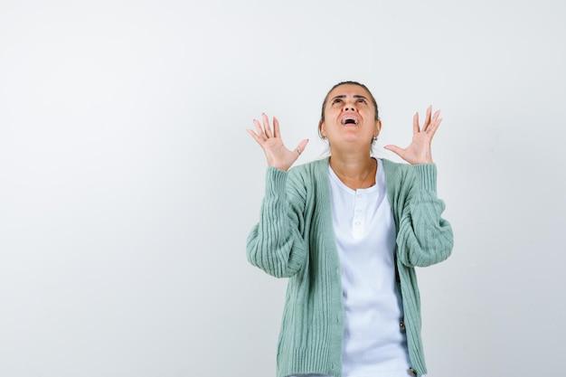 Jeune femme gardant les mains de manière agressive en t-shirt, veste et semblant ennuyée