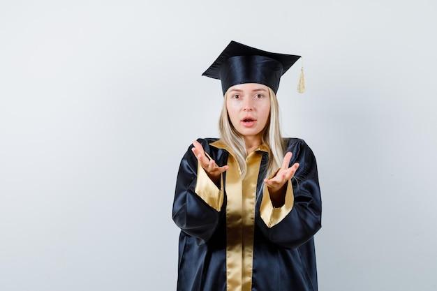 Jeune femme gardant les mains de manière agressive en tenue académique et semblant ennuyée.