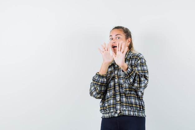 Jeune femme gardant les mains pour se défendre en chemise à carreaux et à la peur, vue de face.