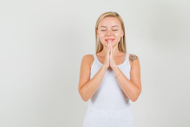 Jeune femme gardant les mains en priant le geste en maillot blanc et à la recherche d'espoir.