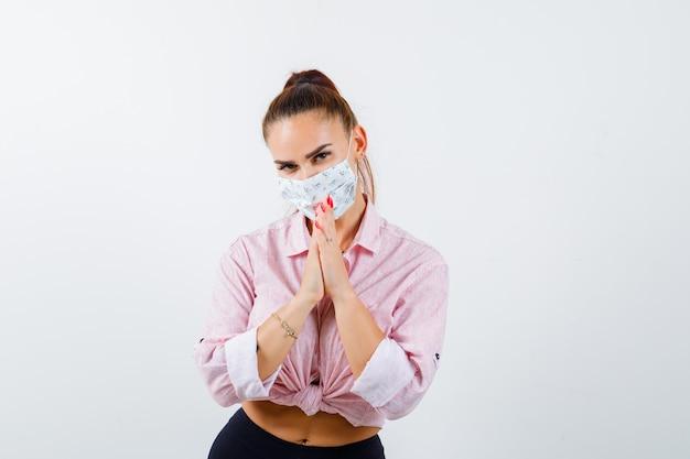 Jeune femme gardant les mains en signe de prière en chemise, masque et à la recherche d'espoir
