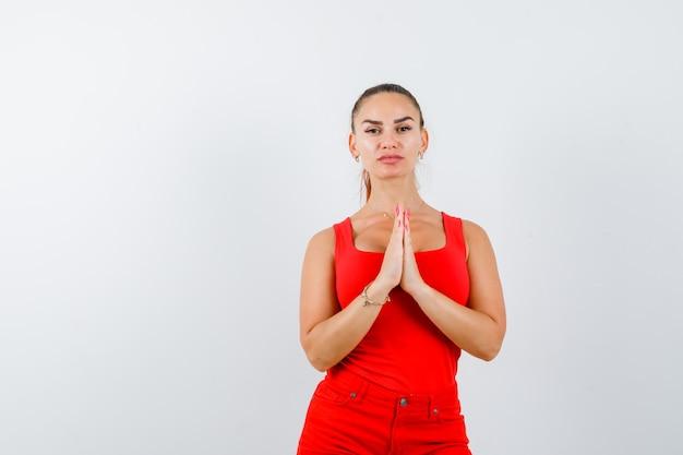 Jeune femme gardant les mains en signe de prière en maillot rouge, pantalon rouge et à la recherche d'espoir. vue de face.
