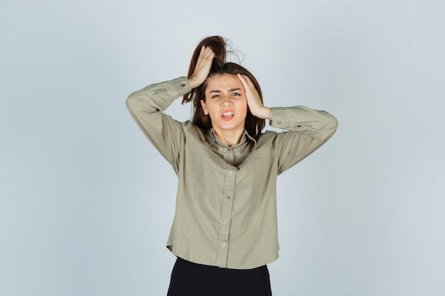 Jeune femme gardant les mains sur la tête en chemise, jupe et semblant irritée. vue de face.
