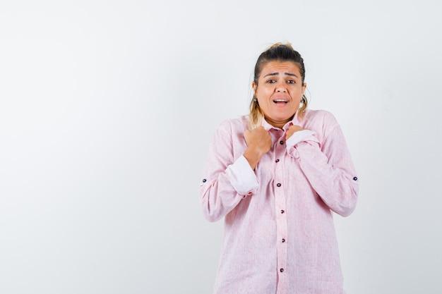 Jeune femme en gardant les poings sur la poitrine en chemise rose et à la confusion