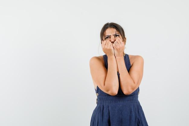 Jeune femme gardant les poings sur le visage en robe et à la peur