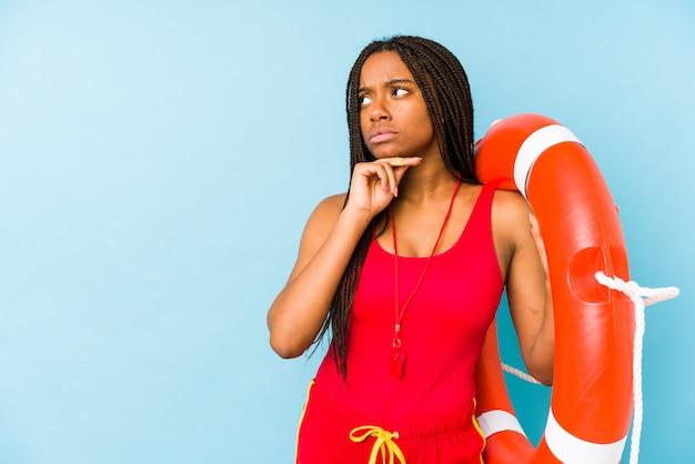 Jeune femme de garde de vie afro-américaine isolée à la recherche sur le côté avec une expression douteuse et sceptique.