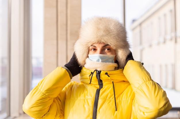 Jeune femme à la gare dans un masque de protection sur le visage en passager de vêtements d'hiver