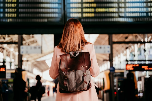 Jeune femme, à, gare, regarder, destination, board. concept de voyage et de transport public