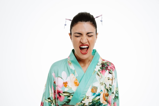 Jeune femme geisha en colère en kimono japonais traditionnel criant avec une expression agacée qui se déchaîne debout sur un mur blanc