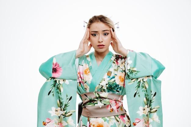 Jeune femme geisha en kimono japonais traditionnel, l'air confus et inquiet, tenant la main sur la tête, debout sur un mur blanc