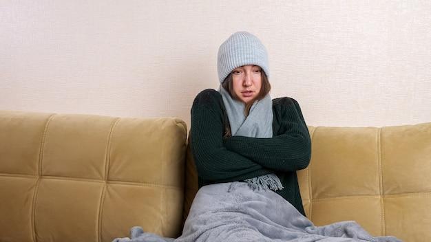 Jeune femme gelée au chapeau recouvert de plaid gris met une écharpe assise sur un canapé moderne dans une chambre froide pendant l'arrêt du chauffage domestique.