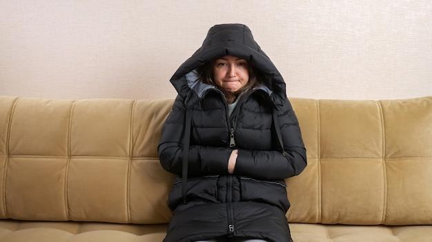 Une jeune femme gelée en colère met une hotte assise sur un grand lit dans une chambre froide pendant l'arrêt du chauffage domestique en hiver