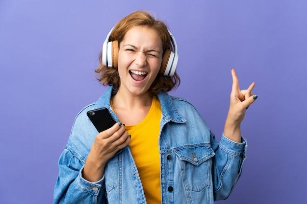 Jeune femme géorgienne isolée à l'écoute de la musique avec un mobile faisant un geste rock