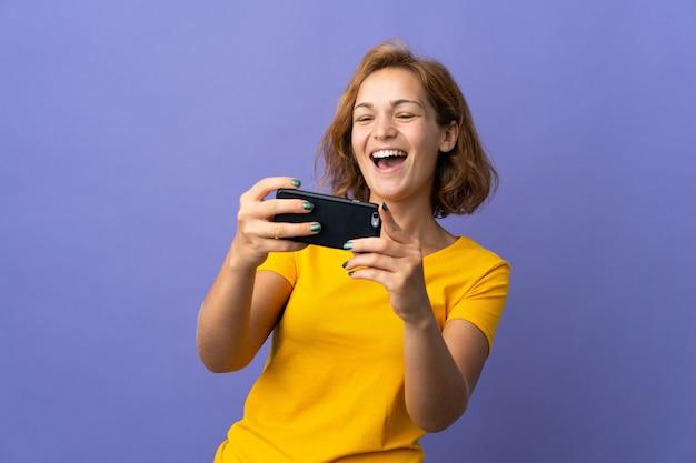 Jeune femme géorgienne isolée sur fond violet jouant avec le téléphone mobile