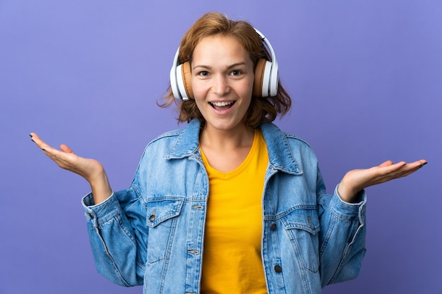 Jeune femme géorgienne isolée sur mur violet surpris et écouter de la musique