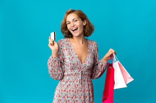 Jeune femme géorgienne avec sac à provisions isolé sur fond bleu tenant des sacs à provisions et une carte de crédit
