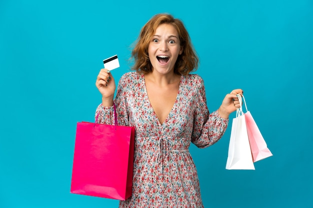 Jeune femme géorgienne avec sac à provisions isolé sur fond bleu tenant des sacs à provisions et surpris