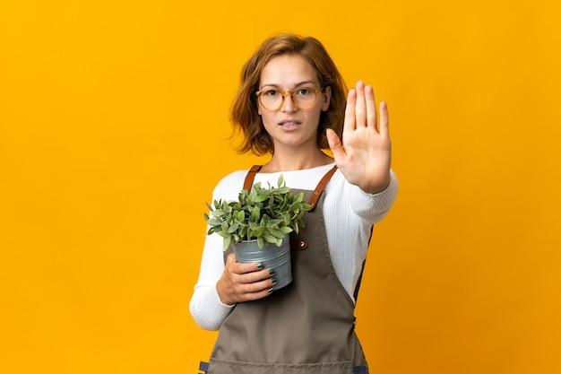 Jeune femme géorgienne tenant une plante isolée sur un mur jaune faisant le geste d'arrêt