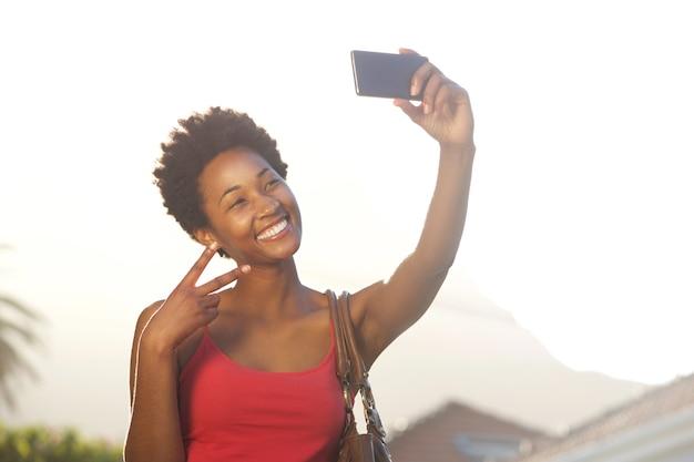 Jeune femme gesticulant signe de paix et de prendre un selfie