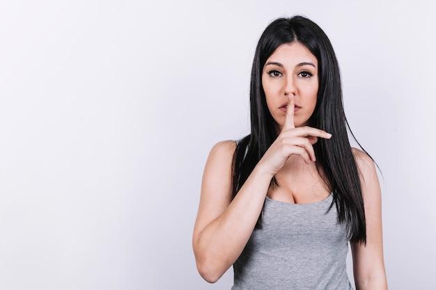 Jeune femme gesticulant silence