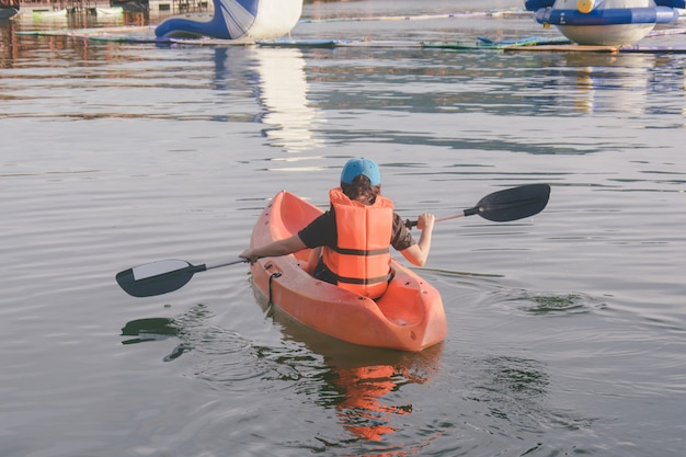 Jeune femme en gilet de sauvetage orange, kayak sur un lac.