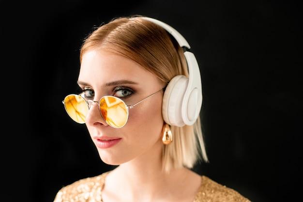 Jeune femme glamour blonde dans un casque blanc et des lunettes de soleil élégantes debout devant la caméra sur fond noir