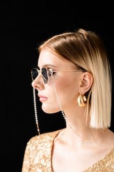 Jeune femme glamour blonde en lunettes de soleil élégantes, robe scintillante et boucles d'oreilles dorées debout devant la caméra