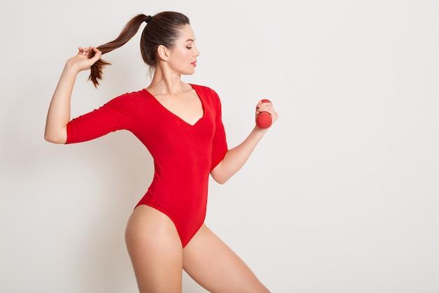 Jeune femme glamour mince avec des cheveux noirs habille une combidress élégante rouge, touchant sa queue de cheval avec une main et détient un haltère avec un autre, vue latérale d'une jolie fille. copiez l'espace pour la publicité.