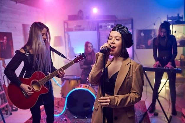 Jeune femme glamour séduisante chantant au micro sur scène