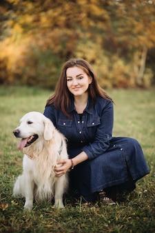 Jeune femme avec un golden retriever dans un magnifique parc d'automne