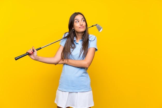 Jeune femme de golfeur sur mur jaune isolé faisant un geste de doutes tout en soulevant les épaules