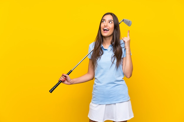 Jeune femme de golfeur sur mur jaune isolé visant à réaliser la solution tout en levant un doigt