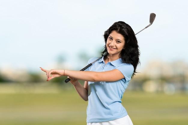 Jeune femme de golfeur pointant sur le côté pour présenter un produit à l'extérieur