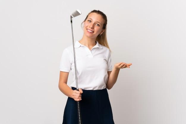 Jeune femme golfeuse sur mur blanc isolé étendant les mains sur le côté pour inviter à venir