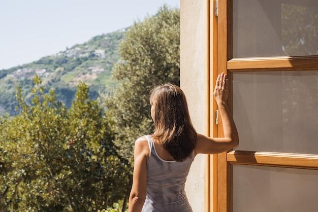 Jeune femme à une grande fenêtre ouverte.