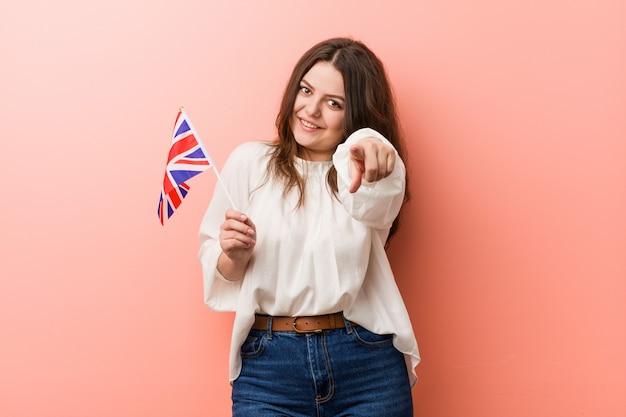 Jeune femme grande taille tenant un drapeau du royaume-uni avec des sourires joyeux pointant vers l'avant.