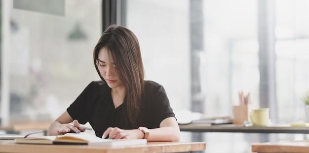 Jeune femme graphiste attrayante en lecture