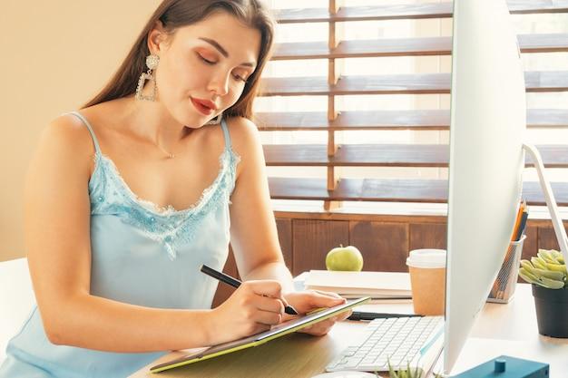 Jeune femme graphiste au travail dans son bureau